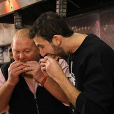Mario Batali and owner Jake Dell biting into sandwiches